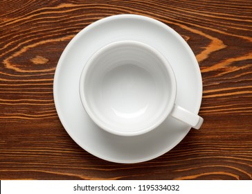 White, clean, empty Cup on a dark wooden background. Top view. close up