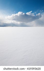 White clear surface of snow till flat horizon and beautiful cloudscape; copy space