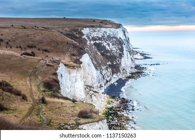 The White Cliffs of Dover, limestone chalk cliffs. Footpath on the edge during sunset. Early spring, Kent County, Dover. Cretaceous chalks