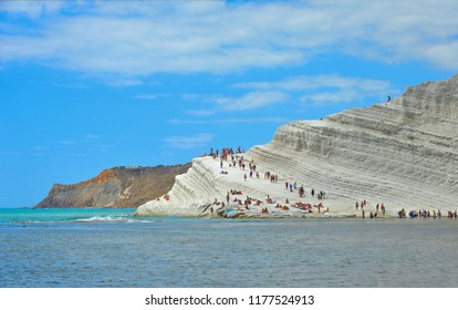 white cliffs naturally made of smooth pug at Scala dei Turchi beach full of people with turquoise mediterranean sea and blue cloudy summer sky near Agrigento, Sicily, Italy