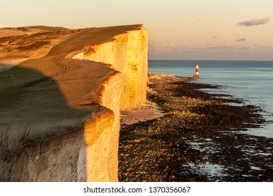 White cliffs of southern UK during colorful autumn sunset. Amazing scene, with stony beach and lighthouse further away. Calm sea as well as peaceful colorful sky almost without clouds.