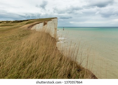 White cliffs of southern UK on a typical cloudy day. Amazing scene, with stony beach and lighthouse further away. Calm and colorful sea with dramatic skies.