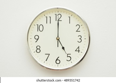 White Clock hanging on a wall showing 5 o'clock