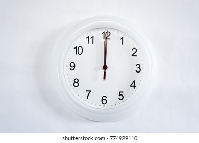 White clock hanging on white wall shows twelve o'clock