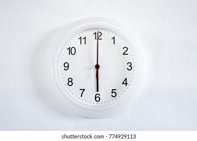 White clock hanging on white wall shows six o'clock