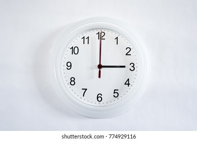 White clock hanging on white wall shows three o'clock