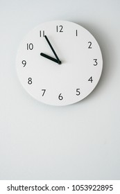 white clock on white backgrounds wall