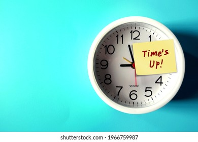 White clock on blue copy space background with note weitten TIME'S UP ,concept of time running out , time management to not miss a due date or a deadline