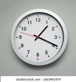 white clock on the gray wall