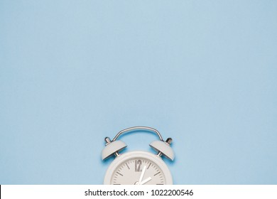 White clock on pastel blue background. Space for copy. Minimal concept.