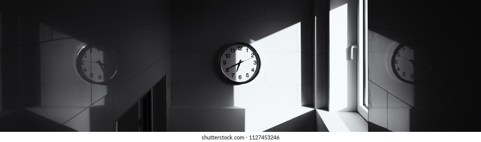 White clock on the wall on the landing. Reflection of the dial on the mirror surface of the walls, the concept of the present, the past and the future. black and white photo.