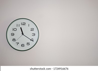 A white clock on the wall to tell the time.