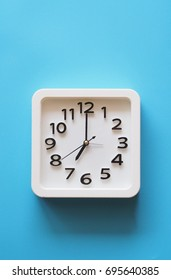 White clock over blue background.