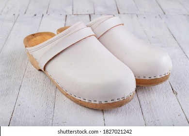 White clogs on a white table. Footwear intended for medical personnel. Light background.