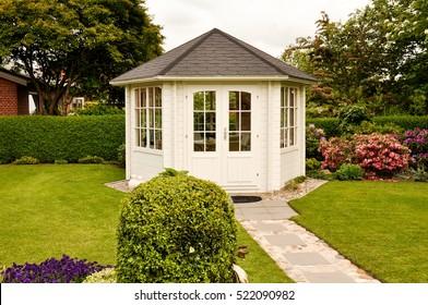 White closed gazebo in garden in summer