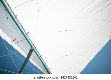 White cloth fabric, masts and ropes close-up on the sail of a tri-yacht or yacht sailing boat