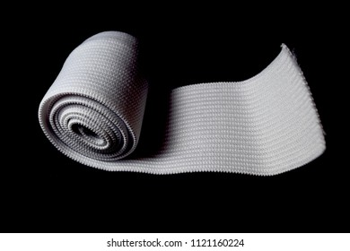 White cloth ribbon on black background. Close up of sewing elastic band