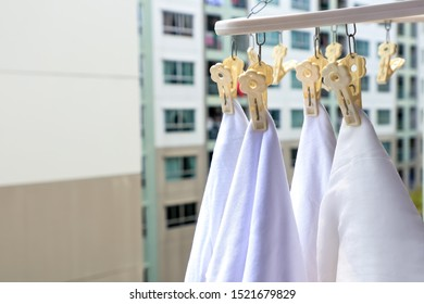 White clothes hang by pegs at balcony of residential, Dry clothes in the sun.