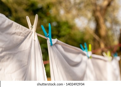 White clothes hung out to dry on a washing line and fastened by the clothes pegs in the bright warm sunny day. Blurred garden at background.