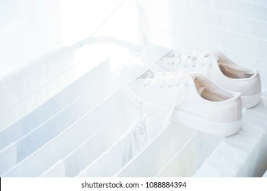 White clothes, towels, sneakers and bed linens in the dryer. Clothing and personal items after washing. Household and cleanliness. Soft focus and beautiful bokeh.