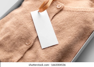 White clothing tag, label blank mockup template with the ribbon, to place your design. On a woolen cardigan in a box, fabric textile background