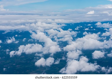 White cloud above the blue sky from airplane window and village landscape.
