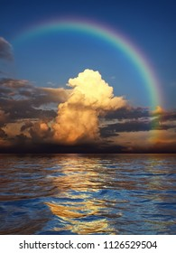 A white cloud in the evening sun under a rainbow over the ocean