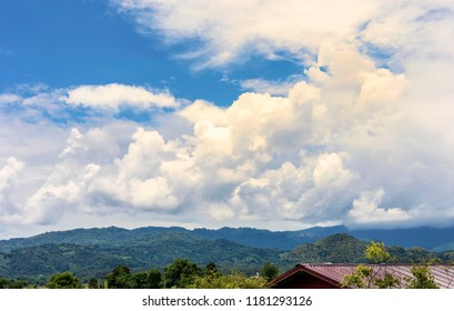White cloud flying on blue sky above mountain and green forest