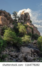 White clouds accent towering piles of granite boulders with sunlit trees and shadows at Watson Lake Prescott AZ.