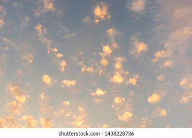 White clouds against the blue sky in the light of the rising sun