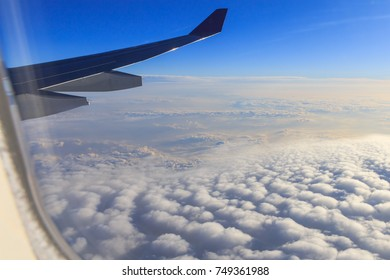 White clouds and blue sky with airplane wing,Look from the plane window