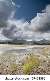 White clouds in blue sky over Irish hills and estuary at Dingle peninsula Kerry district Ireland
