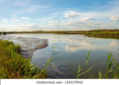 White clouds and a blue sky reflecting in the smooth water surface of a wide creek in the Dutch National Park De Biesbosch. In the background high voltage lines and power pylons are just visible.