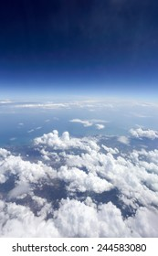 White clouds and blue sky seen from airplane.