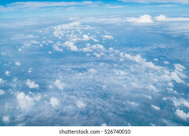 White clouds and blue sky view from airplane window. Beautiful cloudscape from aerial view.