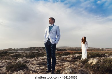 White clouds cover the field full of stones where newlyweds stand