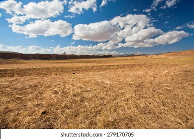 White clouds floating over dry grass land of plateau in Middle East