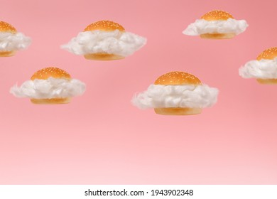 White clouds inside burger buns floating against pink sky background. Surreal fast food hamburger group concept. 2021 minimal abstract summer healthy low calorie diet food idea.