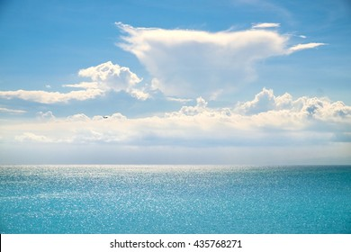 White clouds on blue sky over calm sea. Sunlight reflection on sea, Bali, Indonesia. Sunny sky with fantastic soft clouds and calm ocean, Bali. Summer outdoor nature harmony. Summer holiday serenity.