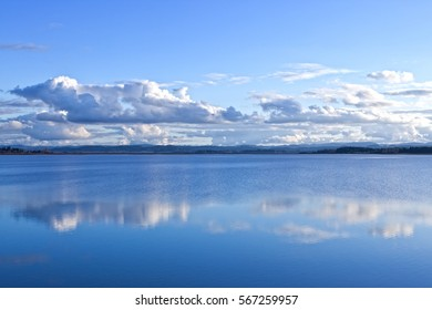 White clouds reflected in a calm blue lake in western Oregon.