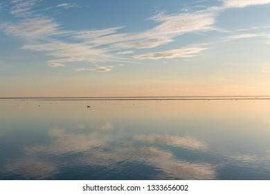 White clouds reflecting in absolutely calm water by the coast of the swedish island Oland in the Baltic Sea