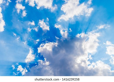 White clouds and sunrays on blue sky