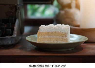 White Coconut Cake on green ceramic dish on wooden table,typewriter,white candle on wooden bowl