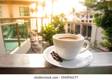 White coffee cup with coffee beans on the balcony in the morning with sunshine, blurred background. Hot coffee after wake up for refreshment in the morning. Coffee time in the concept. - Shutterstock ID 1943956177