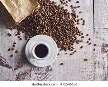 White coffee cup and beans on white wooden table. Top view. Free text space.