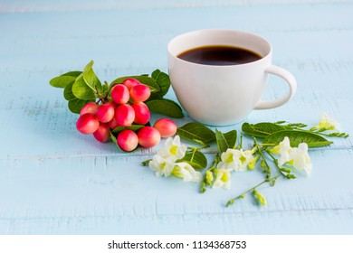 White coffee cup with black coffee ,flowers and fruits on wooden table.