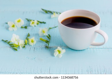 White coffee cup with black coffee and flowers on wooden table.