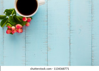 White coffee cup with black coffee and fruits on wooden table.