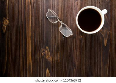 White coffee cup with black coffee and glasses on wooden table.