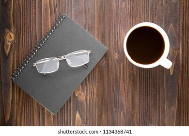 White coffee cup with black coffee ,notebook and glasses on wooden table.